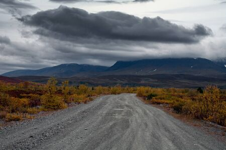 The road to the mountains and a dark cloud over the mountains. Polar Urals. Russia.