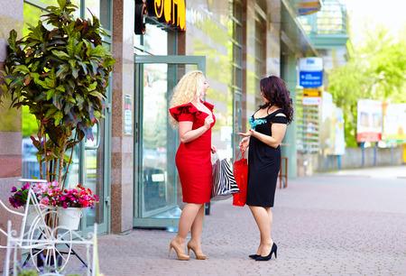 happy plus size women shopping, talking on the street