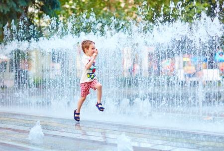 Foto de excited boy running between water flow in city park - Imagen libre de derechos