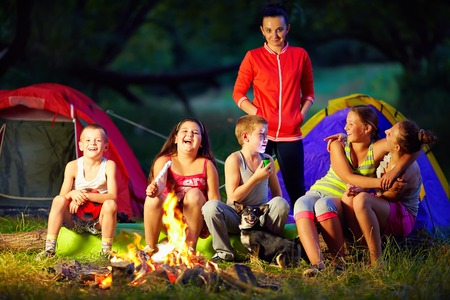 happy kids telling interesting stories around campfire