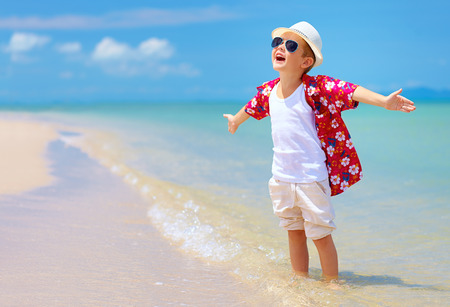 happy stylish boy enjoys life on summer beach