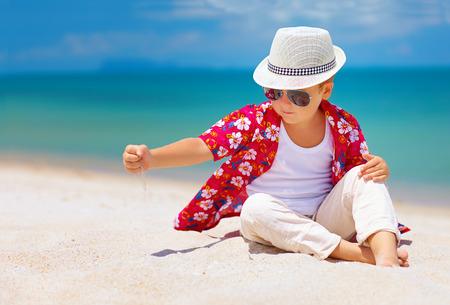 Foto de stylish kid, boy playing with sand on summer beach - Imagen libre de derechos
