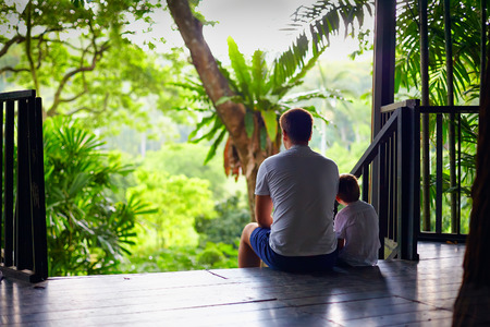 Foto de father and son sitting on tree house stairs in tropical forest - Imagen libre de derechos