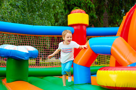 Photo pour happy excited boy having fun on inflatable attraction playground - image libre de droit