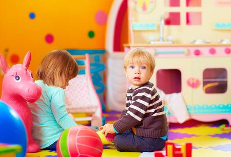 Foto de cute little kids playing together in daycare center - Imagen libre de derechos