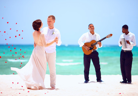 beautiful bride and groom dancing on tropical beach, live music