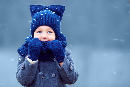 Foto de cute little boy, kid in winter clothes walking under the snow - Imagen libre de derechos