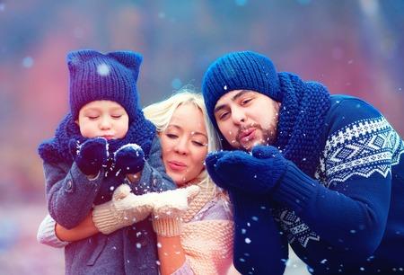 Photo pour portrait of happy family blowing winter snow outdoors - image libre de droit