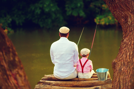 Foto de cute father and son fishing together among beautiful pristine nature - Imagen libre de derechos