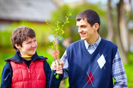 Foto de portrait of happy woman and man with disability together on spring lawn - Imagen libre de derechos