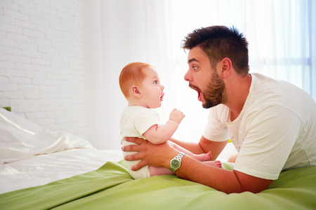 Photo for funny father and baby look at each other with amazement - Royalty Free Image