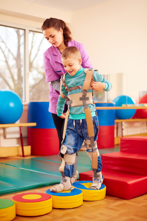 Photo for cute kid having physical musculoskeletal therapy in rehabilitation center - Royalty Free Image