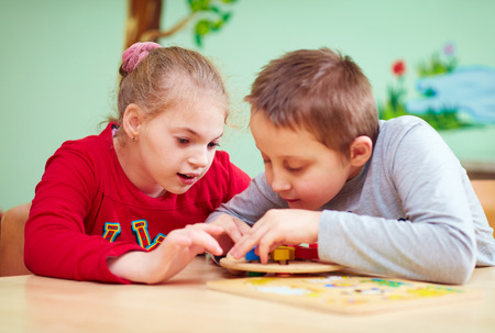 Photo for kids with special needs develop their fine motor skills in daycare rehabilitation center - Royalty Free Image