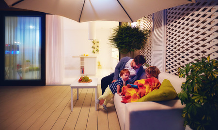 Photo for family relaxing on patio zone with open space kitchen and sliding doors on background - Royalty Free Image