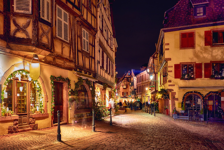 Foto de traditional half-timbered houses on naroow street of Kaysersberg, Alsace, France on christmas eve - Imagen libre de derechos