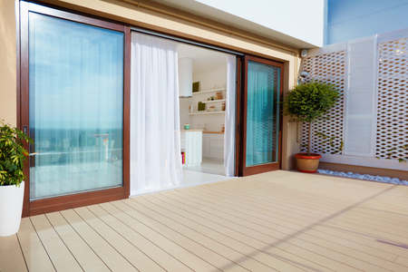 Photo for Roof top patio with open space kitchen, sliding doors and decking on upper floor - Royalty Free Image