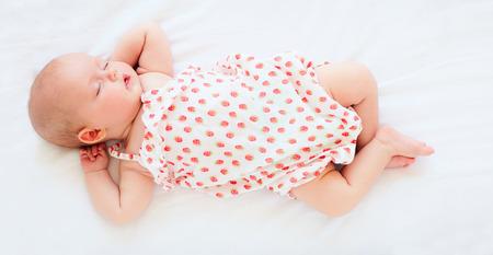 Foto de cute infant baby girl in bodysuit sleeping in bed. top view - Imagen libre de derechos