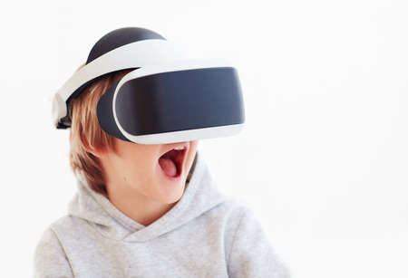 Photo pour excited young boy, kid wearing virtual reality goggles, playing videogames - image libre de droit