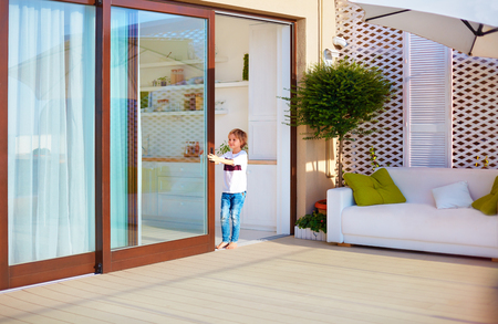 Photo pour happy young boy, kid opening the sliding door on rooftop patio area at home - image libre de droit