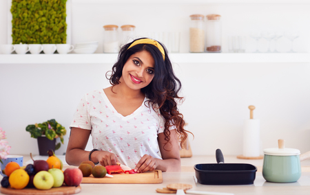 Photo pour beautiful happy young indian woman cutting vegetables on the kitchen, healthy eating - image libre de droit
