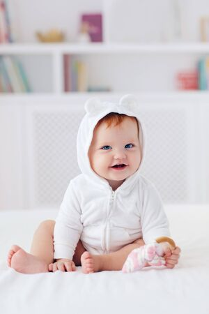 Photo pour happy infant baby girl in funny ear hood is sitting on the bed at home - image libre de droit