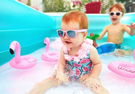 Photo pour cute happy baby girl having fun in kid pool, summer vacation - image libre de droit
