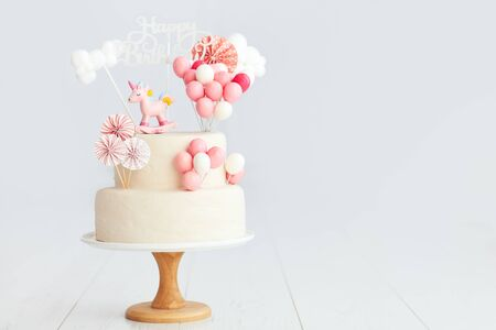 Foto de baby girl birthday cake with unicorn and balloons - Imagen libre de derechos