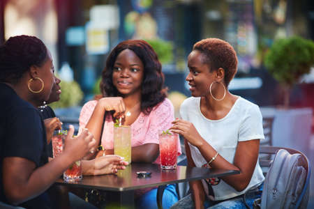 Photo for Happy African American Women, friends sitting together at the outdoor restaurant at summer day - Royalty Free Image