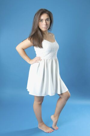 Young girl in a white dress with long hair.Studio photography on a blue background. Age 18 years old girl.