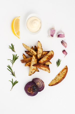 Baked potatoes with rosemary and garlic, served with aioli sauce on a white background.