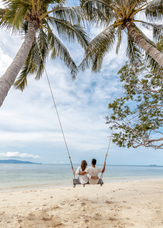 Foto de Young couple swinging on a swing on paradise tropical beach, honeymoon, vacation, travel concept - Imagen libre de derechos