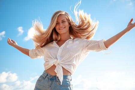 Photo for Beautiful young blonde girl with flowing hair and dimples against the blue sky and the sun, beauty and fashion - Royalty Free Image