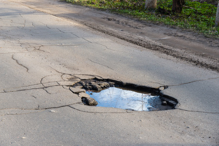 Road hole. Repair work grey asphalt puddle