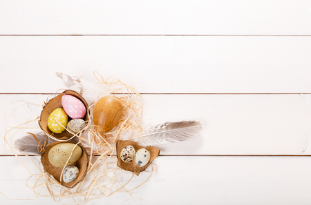 Easter background with Easter eggs, bird feather and spring flowers. Top view with copy space