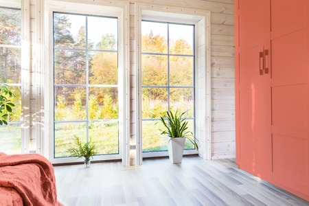 Photo pour Bright interior, room in wooden house with large window. Scandinavian style. color of the year 2019 living coral - image libre de droit