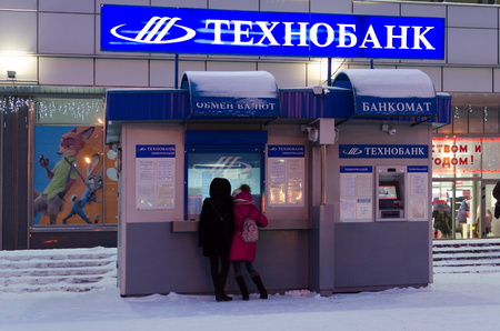 GOMEL, BELARUS - JANUARY 5, 2017: Unidentified girls exchange money in currency exchange Technobank near department store. Nearby is ATM of same bank
