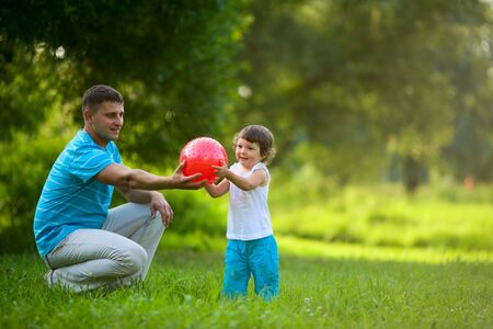 Happy Family playing ball outdoors summer activity