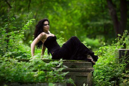 Young beautiful demonic female creature sitting on gravestone