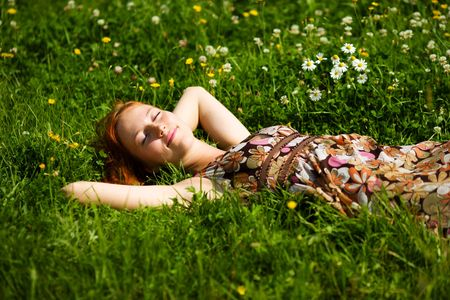 Photo pour Young woman lying in grass dreaming summer day - image libre de droit