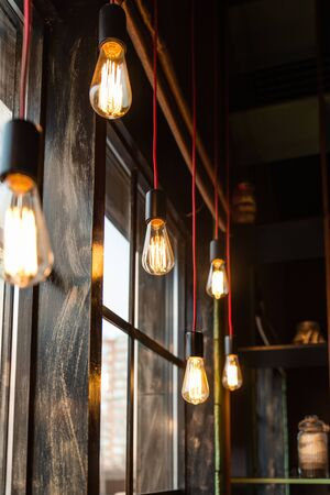 Photo for retro warm light bulbs hang at different levels along the window. red wire wooden window - Royalty Free Image