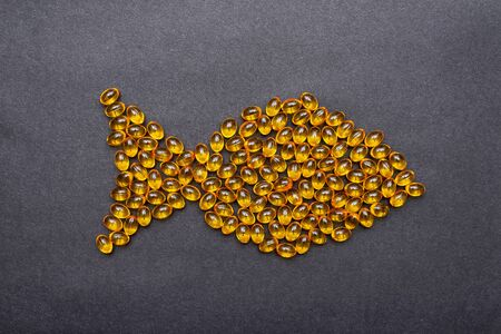 Photo pour Omega 3 capsules laid out in the shape of a fish on black background. Fish oil in pills. Health support and treatment. - image libre de droit