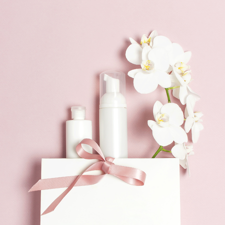 Photo pour Cosmetics SPA branding mock-up. Flat lay top view White cosmetic bottle containers gift bag White Phalaenopsis orchid flowers on pink background. Natural organic beauty product concept. - image libre de droit