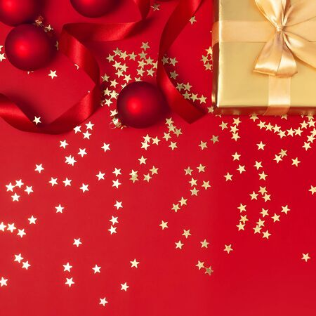 Photo pour New Year Christmas golden presents with ribbon, Christmas balls, gold confetti stars on red background top view. Flat lay Xmas holiday 2020 celebration. Gift boxes greeting card Festive decorations. - image libre de droit