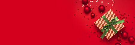 Photo for Christmas background. Gift with green ribbon, red Christmas balls, confetti shape of stars on red background top view. New Year presents Festive decorations Flat lay Xmas holiday 2020 celebration. - Royalty Free Image