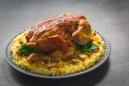Photo pour Kabsa - arabian dish made of long grain basmati rice, whole chicken, onion, spices: cardamom, saffron, cinnamon, bay leaves. Decorated with almonds and raisins. Saudi Arabia food. Grey background - image libre de droit