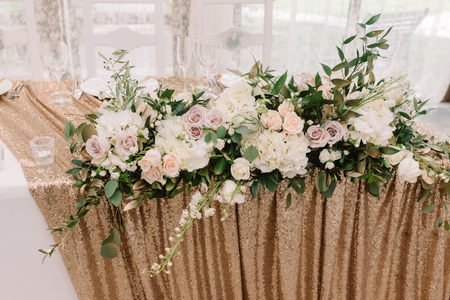 Beautiful pink and lilac roses and white hydrangea on a wedding table. Stylish details of decoration of a table of the groom and bride.