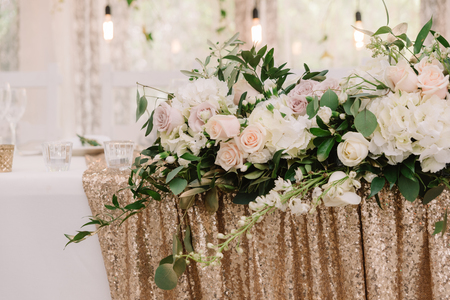 Decoration of a stylish beautiful wedding with flowers and golden fabric with sequins. Wedding presidium