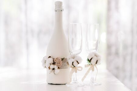 Photo pour A large bottle of wedding champagne decorated lace made of sack and natural cotton. Wedding glasses. Stylish wedding accessories are white in rustic style - image libre de droit