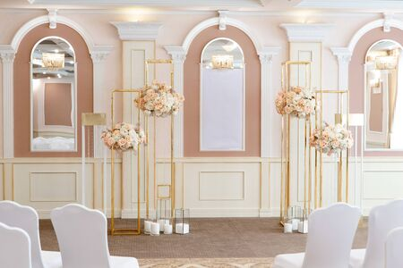 Photo pour Magnificent bouquets from fresh roses and carnations on metal designs. Decoration of a wedding ceremony in hotel - image libre de droit