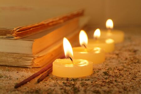 Esoteric atmosphere created with candles, old books and incense